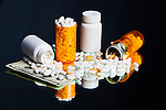 Drugs and Money.  Legal prescription drugs represented with U.S. currency on mirrored badkground.  Conceptual image representing drug culture, medical, insurance, dichotomy, and more.