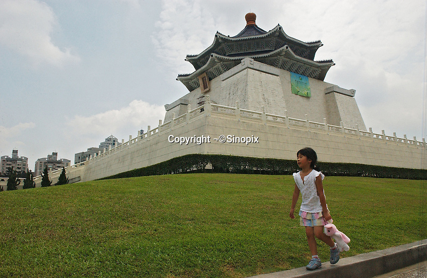 A child walks past the National Taiwan Democracy Memorial Hall, previously known as the Chiang Kai-Shek Memorial Hall. The name-change drive was pushed by President Chen Shui-bian who said that the name changes have restored historical truth and reflect the mainstream opinion of the Taiwanese people. However, the action has sparked strong criticism from the opposition, led by the Kuomintang (KMT), which favors improved ties with Beijing..18 Jun 2007