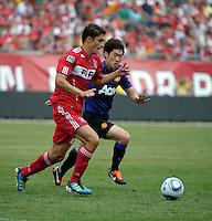Manchester United midfielder Ji-Sung Park (13) pressures Chicago Fire defender Josip Mikulic (23).  Manchester United defeated the Chicago Fire 3-1 at Soldier Field in Chicago, IL on July 23, 2011.