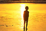 Boy playing on beach at sunset at Venice Beach, CA