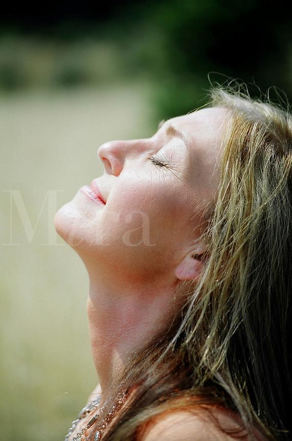 Woman enjoying the sun on her face..MR