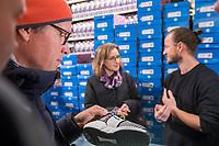 """Adidas-BVG-Turnschuh.<br /> Verkauf des Adidas-BVG-Turnschuh """"Sneaker EQT Support 93"""", im Berliner Turnschuhgeschaeft """"Overkill"""" am Dienstag den 16. Januar 2018.<br /> Der Turnschuh, der auch bis zum 31.12.2018 als BVG-Jahreskarte gueltig ist, wird in einer limitierten Auflage von 500 Stueck verkauft. Jugendlichen und professionelle eBay-Haendler sind bereits seit zwei Tagen Vorort um den Turnschuh fuer 180,- Euro zu kaufen. Die eBay-Haendler wollen den Turnschuh fuer mind. 2.000,-€ verkaufen.<br /> Im Bild: Ein Mann betrachtet den Turnschuh. Hinten vlnr.: Die BVG-Chefin Dr. Sigrid Nikutta und Till<br /> Jagla, Senior Director bei adidas Originals.<br /> 16.1.2018, Berlin<br /> Copyright: Christian-Ditsch.de<br /> [Inhaltsveraendernde Manipulation des Fotos nur nach ausdruecklicher Genehmigung des Fotografen. Vereinbarungen ueber Abtretung von Persoenlichkeitsrechten/Model Release der abgebildeten Person/Personen liegen nicht vor. NO MODEL RELEASE! Nur fuer Redaktionelle Zwecke. Don't publish without copyright Christian-Ditsch.de, Veroeffentlichung nur mit Fotografennennung, sowie gegen Honorar, MwSt. und Beleg. Konto: I N G - D i B a, IBAN DE58500105175400192269, BIC INGDDEFFXXX, Kontakt: post@christian-ditsch.de<br /> Bei der Bearbeitung der Dateiinformationen darf die Urheberkennzeichnung in den EXIF- und  IPTC-Daten nicht entfernt werden, diese sind in digitalen Medien nach §95c UrhG rechtlich geschuetzt. Der Urhebervermerk wird gemaess §13 UrhG verlangt.]"""