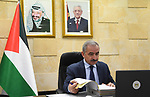 Palestinian Prime Minister Mohammad Ishtayeh, chairs the weekly meeting of his government, via a video link in the West Bank city of Ramallah, on March 1, 2021. Photo by Prime Minister Office