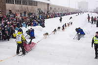 March 3, 2012 Rookie musher Pat Moon runs down 4th avenue after leaving the Ceremonial Start line of Iditarod 2012 in Anchorage, Alaska.