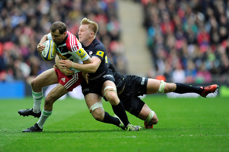 Nick Evans of Harlequins is tackled by Jackson Wray and Alistair Hargreaves of Saracens