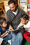 Education Preschool Headstart 3-4 year olds young male teacher reading to two girls