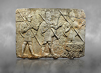 Hittite monumental relief sculpted orthostat stone panel from the Herald's Wall. Basalt, Karkamıs, (Kargamıs), Carchemish (Karkemish), 900-700 B.C. Military parade. Anatolian Civilisations Museum, Ankara, Turkey. Two helmeted soldiers in short skirts carry the shield on their backs and the spears in their hands.  <br /> <br /> Against a grey art background.