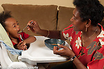 16 month old toddler baby boy in high chair fed soup by great grandmother who takes care of him during the week horizontal