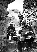 Lieut. Col. R. D. Garrett, chief signal officer, 42nd Division, testing a telephone left behind by the Germans in the hasty retreat from the salient of St. Mihiel.  Essey, France.  September 19, 1918.  Cpl. R. H. Ingleston.  (Army)<br /> NARA FILE #:  111-SC-23112<br /> WAR & CONFLICT BOOK #:  617