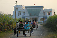 Indien U.P. Meerut .Kontrast im Dorf Kurali , Ochsenkarren vor Spiegelfassade von Gebäude eines lokalen BJP Poltiker - Moderne Tradition Kontraste modernes modern Palast Paläste Reichtum / INDIA UP Meerut .contrast in village Kurali, bullock cart in front of modern building of local BJP politician