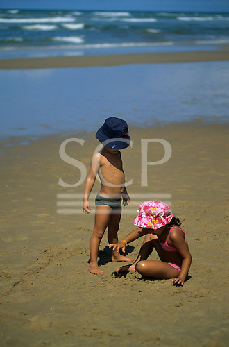 Sauipe, Bahia State, Brazil. Two young children wearing sun hats playing on the sand on a glorious beach.