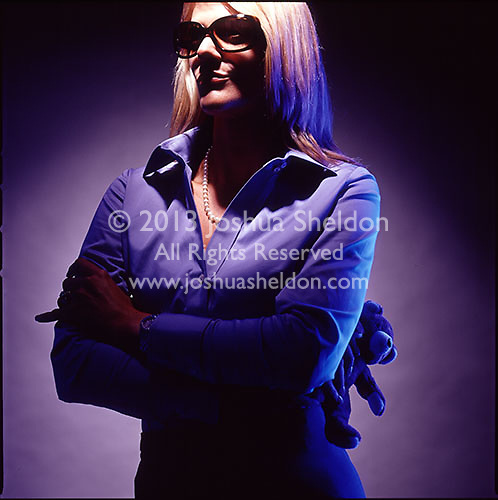 Dramatically lit photograph of blond woman with dark sunglasses holding teddy bear<br />