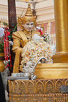 Myanmar, Burma.  Shwedagon Pagoda, Yangon, Rangoon.  A nat, a protective spirit, stands behind a Buddha covered with flower garlands.  Silver cups are for pouring water over the Buddha in a purification ritual.