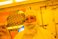 Aeronautics and Astronautics Ph.D. candidate Louis Perna is seen here in the clean room of the Technology Research Laboratory in the Microsystems Technology Laboratory at MIT in Cambridge, Massachusetts, USA. Perna is reflected in a silicon wafer from which he creates both the extractor grid and emitter chip frame for the ion Electrospray Propulsion System (iEPS) for CubeSats project at MIT.  One side has a purple hue due to 300 nanometers of oxide grown on the wafer. <br /> <br /> Researchers in the cleanroom have to wear a bunny suit or clean room suit while working to prevent contamination. Perna works on silicon MEMS fabrication and packaging in the ion Electrospray Propulsion System (iEPS) for CubeSats project at MIT. The iEPS device is used to maneuver a 10cm cubic satellite in space. Two Ph.D. candidates working on the project, Natalya Brikner and Louis Perna have formed a company, Accion Systems Incorporated, to commercialize the research. Brikner, graduating in Winter 2014, is CEO of the company, and Perna is co-founder.
