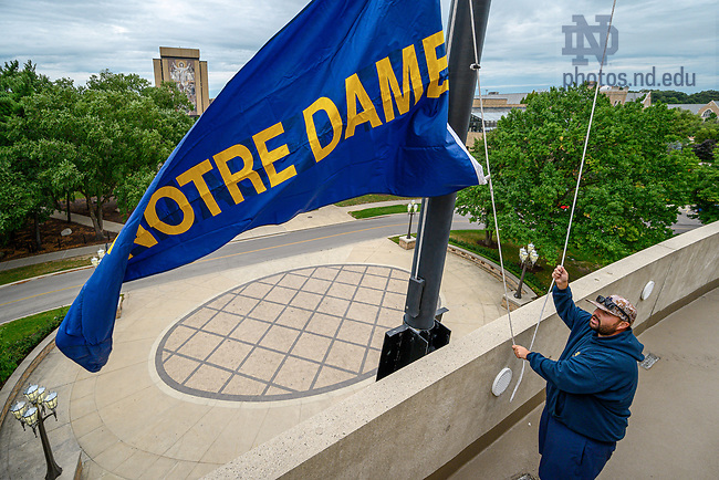 """August 26, 2019; Notre Dame Stadium groundskeeper Robert """"Chip"""" Miltenberger raises the Notre Dame pennant on the Monday of the first game week of the 2019 football season. (Photo by Matt Cashore/University of Notre Dame)"""