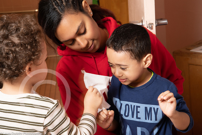 Education preschool 3-4 year olds boy holding out tissue as teacher comforts crying classmate