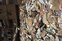 2011 Mokattam Garbage City (alla periferia del Cairo) il quartiere copto dove si vive in mezzo alla spazzatura raccolta: un cumulo di rifiuti (carta e cartone) differenziati. Sul fondo un palazzo con panni stesi ai balconi.