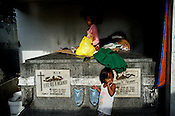 A young girl looks on while her grandmother sits on top of a tomb at the Manila North Cemetery in Manila, Philippines. The scarcity of land and ever growing population has led the local filipinos to live in the same space around the graveyards in the Cemetary. Photo: Sanjit Das