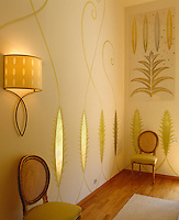 The bedroom walls are hand-painted by Emma Foale with an ornate gold motif and are lit by bespoke brass wall lights