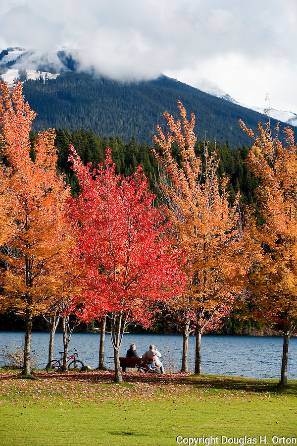 Two friends visit on bench in Rainbow Park, Alta Lake, as first snows dust Whistler Mountain in background.  Whistler and Blackcomb, British Columbia, Canada are regal in fall color while snow begins to dust the mountains during September and October.