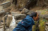 Nepal Nepali man drinking from public water fountain along trail in Solukhumbu remote near Mt Everest  50