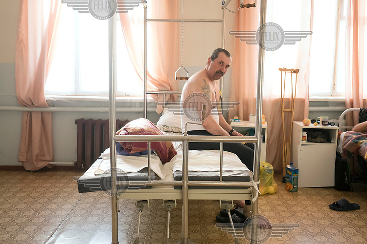 Leonid (56) siting on a bed in Turukhansk district hospital. <br /> He arrived by helicopter from Svetlogorsk after injuring his leg.