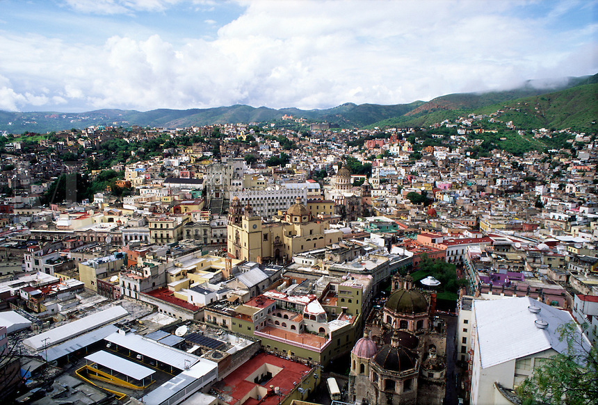 Aerial view of Colorful Mexican cityscape, puffy clouds, mountains in background #5826. Guanajuato, Mexico.