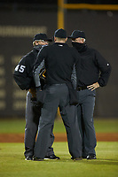 (L-R) Umpires Kevin Morgan, Drew Meadows, and Robert Dunnigan huddle to discuss a call during the NCAA baseball game between the St. John's Red Storm and the Western Carolina Catamounts at Childress Field on March 13, 2021 in Cullowhee, North Carolina. (Brian Westerholt/Four Seam Images)