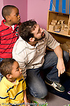 Education Preschool 4-5 year olds two boys and male teacher looking at something to the side vertical