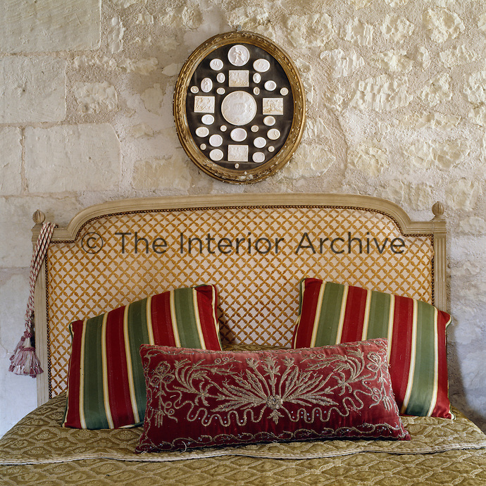 A pair of striped cushions brings a touch of colour to the headboard of this Louis XVI bed against the stone wall of this bedroom