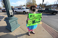 Ruth Mobley, assistant principal at Washington Elementary School, holds a sign up Thursday, Nov. 19, 2020, asking cars to honk as she stands in a tutu and tiara on the corner of Lafayette Street and College Avenue in Fayetteville. Mobley agreed to hold the sign if the students at the school would collect 500 boxes of macaroni and cheese for the school district food pantry and 200 pairs of socks for 7 Hills Homeless Center in Fayetteville. Check out nwaonline.com/201120Daily/ and nwadg.com/photos for a photo gallery.(NWA Democrat-Gazette/David Gottschalk)