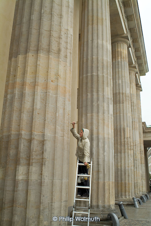 A conservator carries out restoration work on the Brandenburg Gate in central Berlin