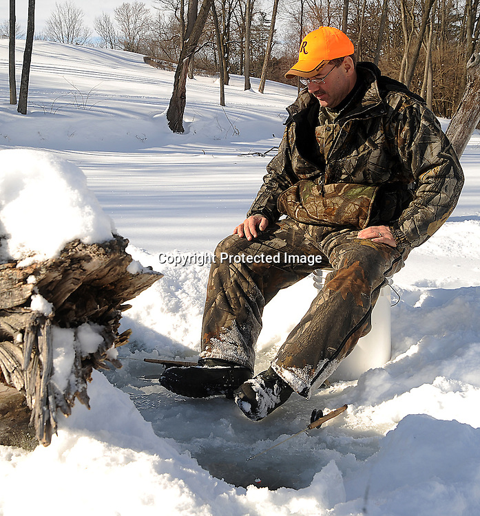Staff Photo/Mike Ullery.Jim Peterson of Piqua watches his poles while ice fishing on Echo Lake Saturday morning.