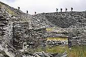 Walkers pass an abandonned slate quarry,high above the Croesor Valley and Tan y Grisiau in the Snowdonia National Park.