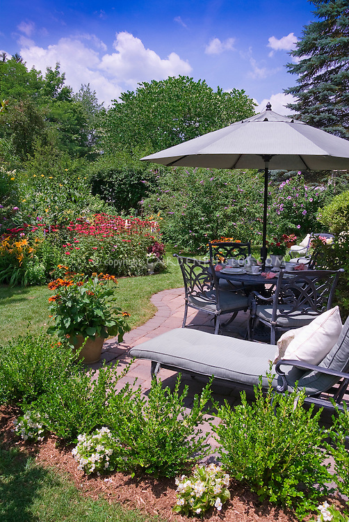 Gorgeous summer backyard landscaping and view of flower garden scene, with patio furniture, umbrella, table set for eating lunch outdoors, chairs, lounge chaise, sunny blue sky and white clouds, Rudbeckia in planter pot container, shrubs, trees, evergreens, boxwood Buxus, Monarda beebalm, perennials and annual plants, begonias, daylilies Hemerocallis, butterfly bush Buddleia. mulched bed, curves, lawn grass - a colorful outdoor living room spa