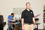 September 18, 2014. Raleigh, North Carolina.<br />  Chuck Sawyer's stores screen print 1000's of t-shirts a week when busy. Here he poses for a portrait in the production part of his main store, while employee Tony Rakes prepares some shirts.<br />  Chuck Sawyer, 37, is the owner of three Instant Imprints franchises, specializing in promotional materials such as t-shirts,signs and mugs. Sawyer wishes he had more saved for retirement and is encouraging his none employees to start thinking about how they will save for when they get older.<br /> Publication: AARP Bulletin<br /> Editor: Jenna Isaacson-Fuller<br /> Model Released<br /> Portrait