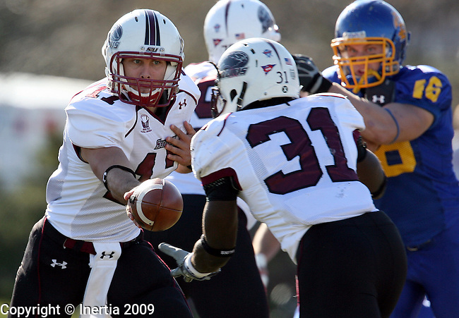 BROOKINGS, SD - NOVEMBER 7:  Quarterback Paul McIntosh #17 of Southern Illinois hands the ball off to teammate Deji Karim #31 against South Dakota State University in the first quarter of their Missouri Valley Conference game Saturday afternoon at Coughlin Alumni Stadium in Brookings. (Photo by Dave Eggen/Inertia).