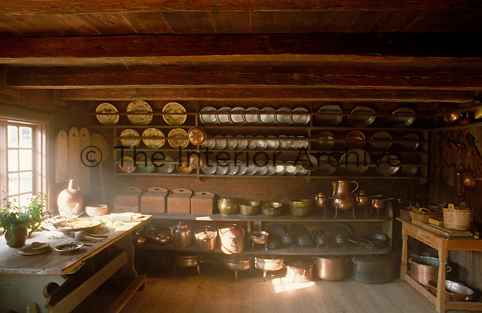 The wall in this country kitchen is lined with pewter and copper plates and utensils