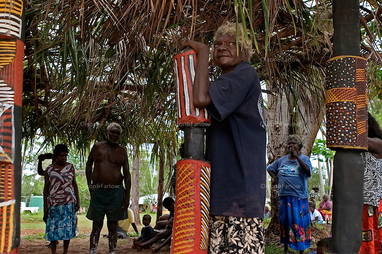 A woman stand next to a pukamani pole for a cleansing ceremony on Tiwi Islands.  A cleansing ceremony is the final ceremony in the death of a family member.  A year or so after the funeral the family gets together and paints pukamani poles and places them around the grave.  Some communities won't say the name of the deceased or go back into the home until there is a big cleansing rain.  But rituals vary from community to community.