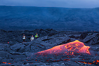 Around sunset, visitors marvel at the glowing molten lava flowing down the hill at (Hawai'i) Volcanoes National Park, Hawai'i Island.