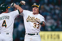 OAKLAND, CA - Jose Canseco of the Oakland Athletics does a forearm bash with teammate Carney Lansford after hitting a home run a game at the Oakland Coliseum in Oakland, California in 1988. Photo by Brad Mangin