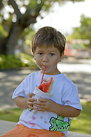 A boy eats a shave ice or snow cone in Kailua, Oahu, Hawaii.