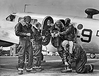 Students receiving familiarization with flight photography at Chevalier Field.  About to board an SNB for a mapping flight.  The K17 mapping camera is being put aboard.  Men have their oxygen masks and heavy flight clothing.  Pilot looking out of forward window is 1st Lt. Maurice E. Pipkin, Jr. UMCR.