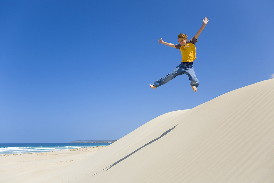 Boy jumping in sand dune