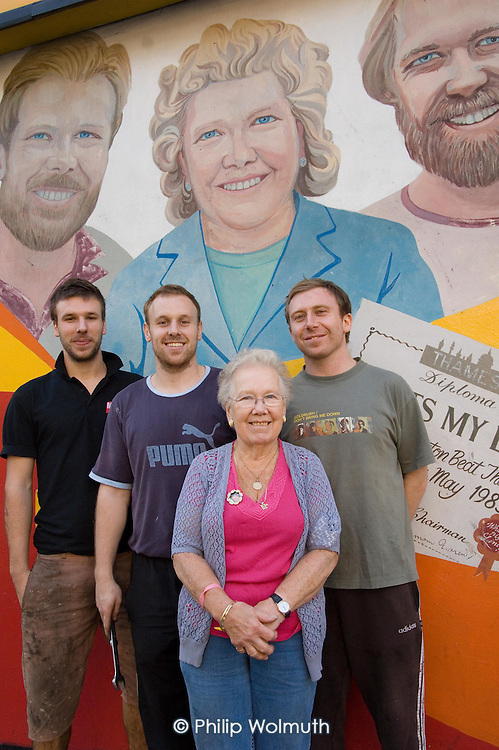 Noreen Hannington with three of her grandchildren, in front of a mural of herself and her two sons outside the Tyre and Wheel Company, Harrow Road.