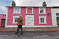 Pictured: A man walks past a house with a visible line of the level the flood reached in New Road.<br /> Re: Cleanup after storm Dennis in Crickhowell, Wales, UK.