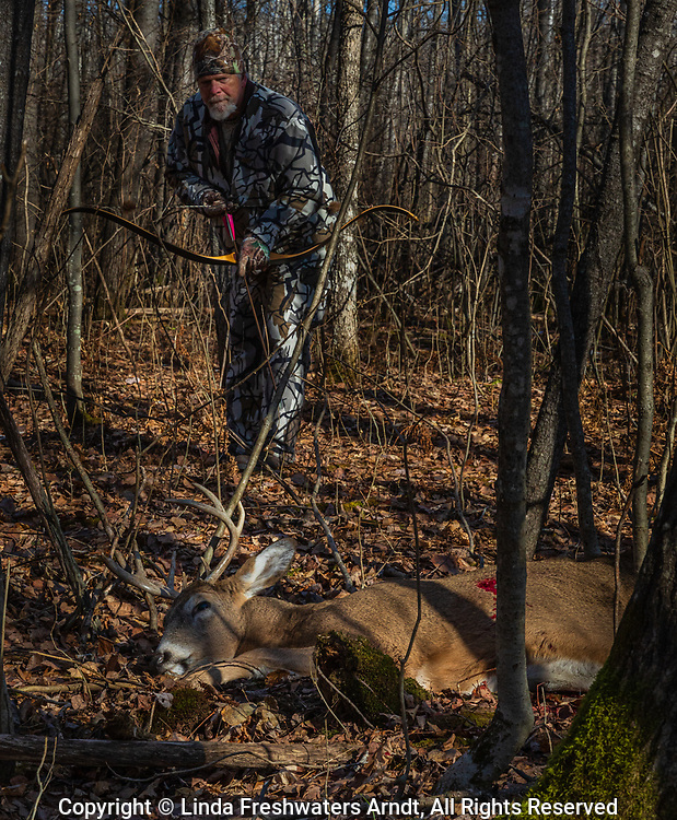 Hunter holding his custom-made recurve bow and arrow as he approaches his kill in northern Wisconsin.