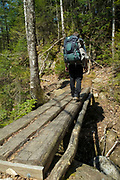 Appalachian Trail - A hiker on the Appalachian Trail just south of Mount Cube crosses a wooden foot bridge in New Hampshire USA