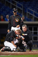 Quad Cities River Bandits catcher Trent Woodward (18) gets checked out by athletic trainer Corey O'Brien as manager Josh Bonifay looks on during the second game of a doubleheader against the Wisconsin Timber Rattlers on August 19, 2015 at Modern Woodmen Park in Davenport, Iowa.  Quad Cities defeated Wisconsin 8-1.  (Mike Janes/Four Seam Images)