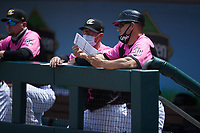Charlotte Knights manager Wes Helms (right) checks his notes during the game against the Gwinnett Stripers at Truist Field on May 9, 2021 in Charlotte, North Carolina. (Brian Westerholt/Four Seam Images)